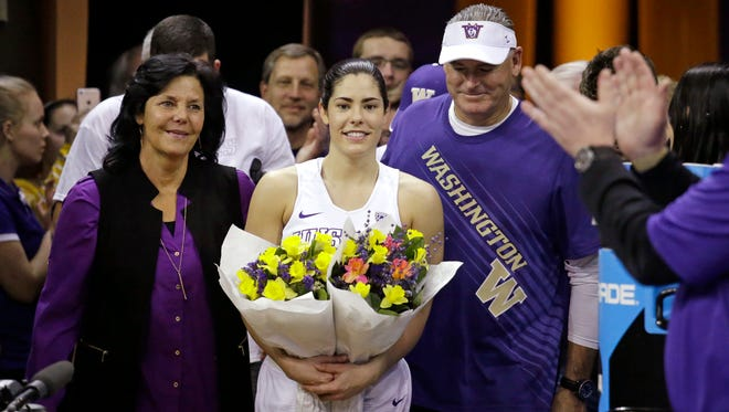 Washington's Kelsey Plum, center, walks onto the court with her parents Katie and Jim Plum for senior night activities after an NCAA college basketball game against Utah Saturday, Feb. 25, 2017, in Seattle. Washington won 84-77. Plum scored 57 points and set the new all-time career NCAA scoring record of 3,397 points during the game. Washington won 84-77. (AP Photo/Elaine Thompson)