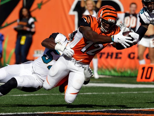 Cincinnati Bengals wide receiver Mohamed Sanu, right, dives into the end zone for a touchdown as he's tackled by Jacksonville Jaguars outside linebacker J.T. Thomas during the first half of an NFL football game in Cincinnati, Sunday, Nov. 2, 2014. (AP Photo/David Kohl)