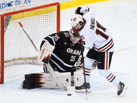 St. Cloud State's Patrick Newell tries to slip the puck past Nebraska-Omaha goalie Evan Weninger during the first period Friday, Dec. 9, at the Herb Brooks National Hockey Center.