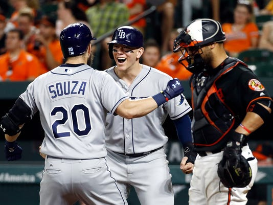 Tampa Bay Rays' Logan Morrison, center, greets Steven Souza Jr. at home plate next to Baltimore Orioles catcher Welington Castillo, right, after scoring on Souza's three-run home run during the 10th inning of a baseball game in Baltimore, Friday, June 30, 2017. Tampa Bay won 6-4 in 10 innings. (AP Photo/Patrick Semansky)