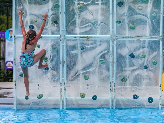A young swimmer tries her hand at The Wall at The Waterpark at the Monon Community Center in Carmel is a 3.5-acre aquatic experience. Surf the waves on the FlowRider, scale the wall of the AquaClimb and ride down the lazy river. Wednesday, July 18, 2018.