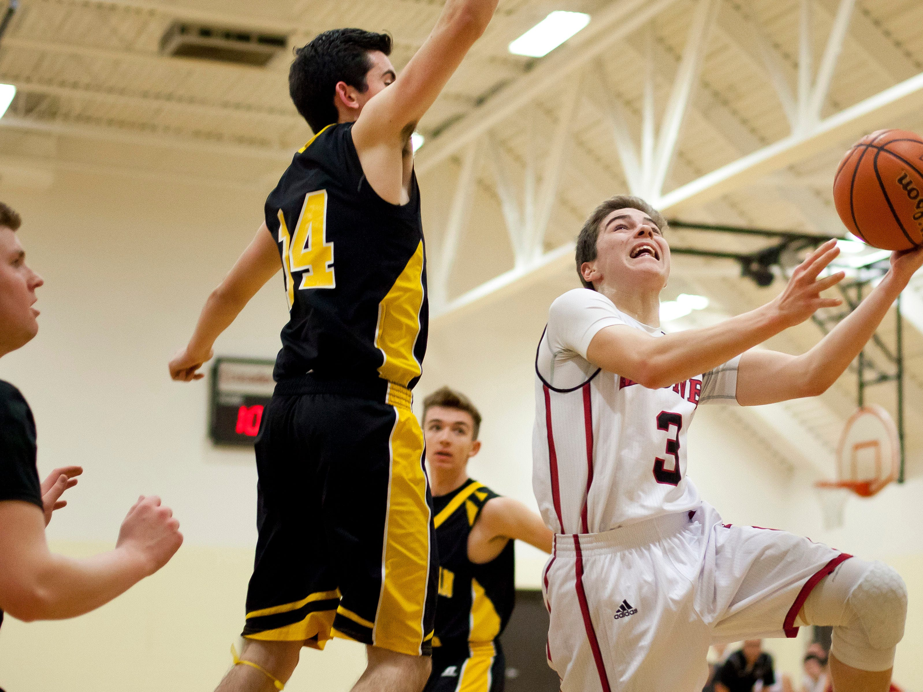 Cardinal Mooney freshman Daniel Everhart goes for a layup as Lutheran North senior Jamesen McHale attempts to block during a basketball game Tuesday, Feb. 17, 2015 at Cardinal Mooney High School in Marine City.