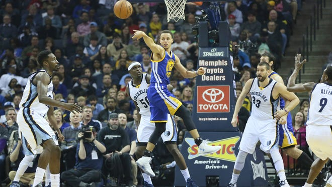 Golden State Warriors guard Stephen Curry (30) passes the ball out of the lane in the first half as Memphis Grizzlies forward Zach Randolph (50) looks on at FedExForum.