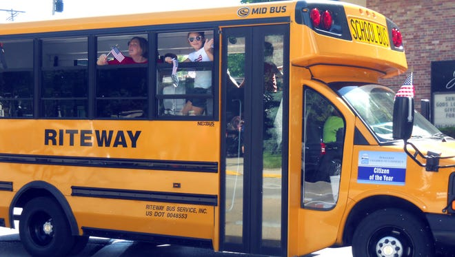 Pewaukee Schools Superintendent JoAnn Sternke waves from a school bus in a parade.