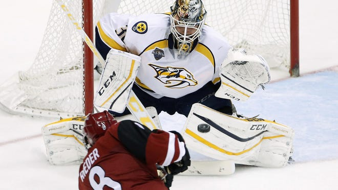 The Predators' Carter Hutton, right, gets ready to make a save on a shot by the Coyotes' Tobias Rieder (8) in the second period Saturday.