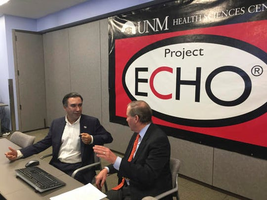 In this Dec. 14, 2016 photo, Project ECHO Director Sanjeev Arora (left) talks with Sen. Tom Udall, D-N.M., about a model for mentoring physicians in isolated rural areas that could be expanded under legislation signed in December by President Barack Obama.