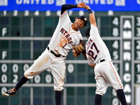 FILE - In this Aug. 30, 2016, file photo, Houston Astros' Carlos Correa (1) and Jose Altuve celebrate the Astros' 3-1 victory over the Oakland Athletics in a baseball game, in Houston. Now that the Cubs have broken baseball's oldest curse, who's next? No team from Texas has ever won the World Series.