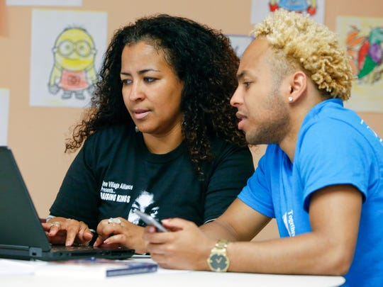 Chandra Pitts of One Village Alliance helps her son, Jahlihl ChAndre, as he works on an internship application at the One Village Alliance in Wilmington Thursday.