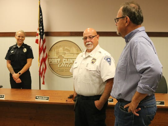 Port Clinton Police Chief Rob Hickman speaks with John Pugh after swearing in his daughter, Amy Pugh, the department's first female full-time patrol officer.