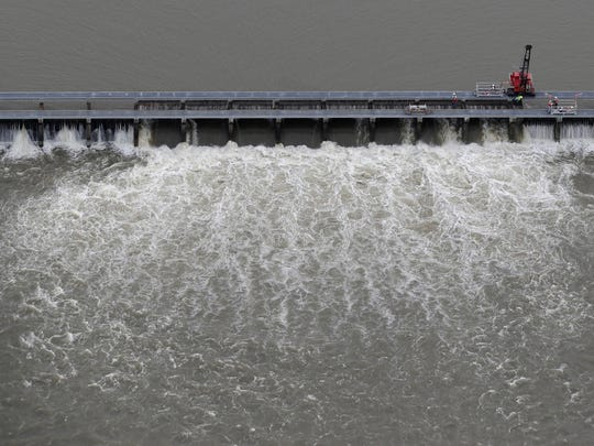 Workers open bays of the Bonnet Carré Spillway to divert rising water from the Mississippi River to Lake Pontchartrain, upriver from New Orleans. The river is now low enough to allow the spillway to be closed.