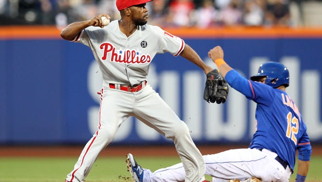 Philadelphia Phillies shortstop Jimmy Rollins (11) forces out New York Mets center fielder Juan Lagares (12) on a ball hit by New York Mets right fielder Curtis Granderson (not pictured) during the first inning Aug. 29 at Citi Field. Credit: Brad Penner-USA TODAY Sports