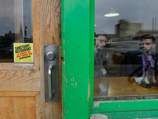 "In this Wednesday, Jan. 18, 2017 photo, a sanctuary restaurant sign is shown on the door of the Russell Street Deli in Detroit. Dozens of restaurants are seeking ""sanctuary"" status, a designation owners hope will help protect employees in an immigrant-heavy industry and tone down fiery rhetoric sparked by the presidential campaign."