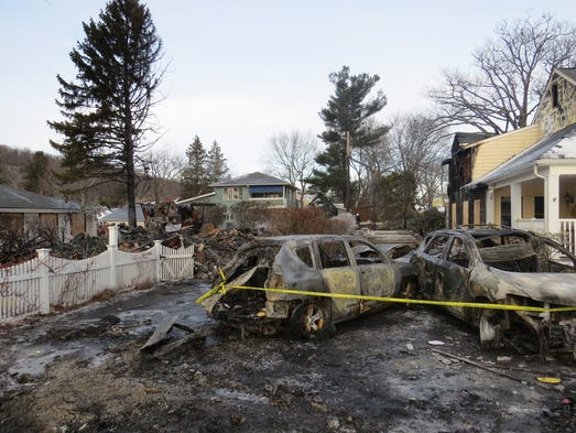 Burnt-out cars are seen in front of a home completely
