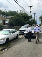 Knoxville Police Department detectives walk toward 1417 McSpadden Street, where a body was reportedly found on Sept. 19, 2017
