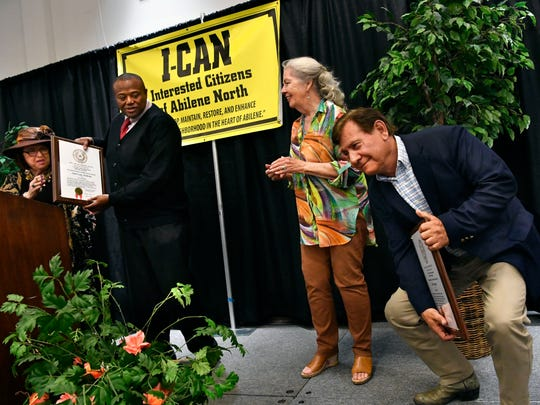 Billy Enriquez clowns about the weight of the ICAN Hero award as Abilene Mayor Anthony Williams also gives the same award to Anita Lane McBride Thursday.
