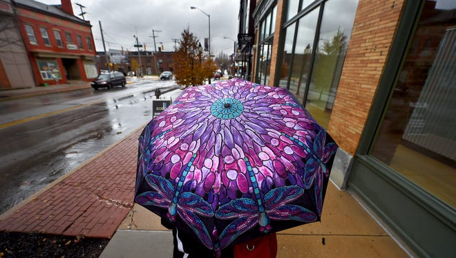 The umbrella of Mary Helwig is a bright spot on the rainy day as she walks along North George Street in York city on Tuesday, Nov. 29, 2016.