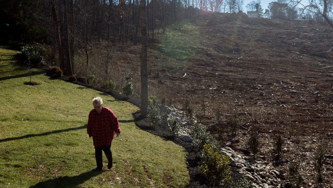Dolores Schaffer walks carefully through her backyard on Wednesday, Jan. 31, 2018, which is currently abutted by cleared landscape where a new subdivision, Westland Oaks, is being built behind her property.