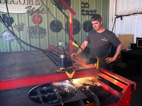 Keith Wineinger, owner of The Burn Shop, runs the CNC plasma cutter on a sheet of steel to create custom designs and signs.