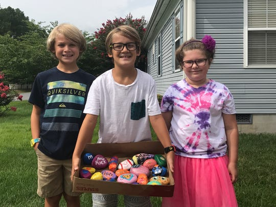 From left to right, Jonah DeVito, Olivia Koval and Zane DeVito proudly display the painted rocks they've been dispersing around their community in Ocean Pines.