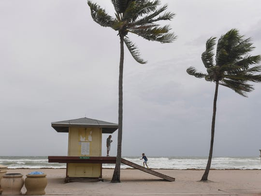 Stan Cohen and his grandson Cooper, 7, play on the lifeguard stand in Hollywood, Florida.
