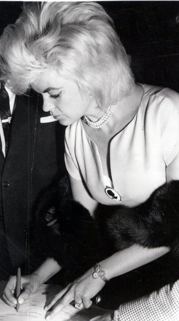 Blonde actress Jayne Mansfield is shown signing her