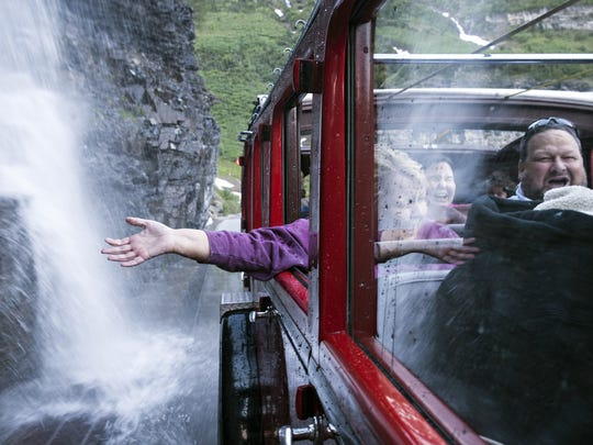 In this photo taken July 2, 2014, passengers in a red bus are splashed by water at the weeping wall along Going-to-the-Sun Road in Glacier National Park.
