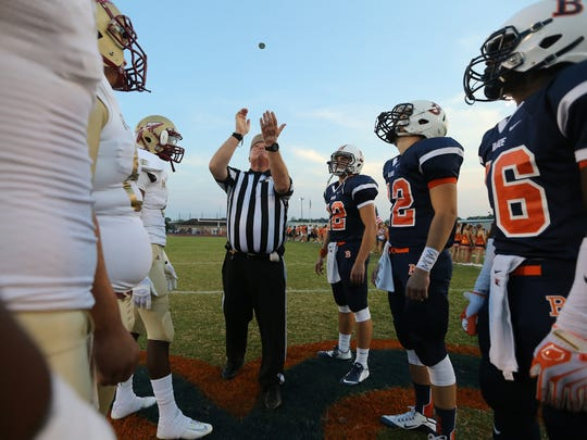 Referee Bobby Garrison flips the coin before the start of the Blackman vs. Riverdale game, at Blackman, on Friday Sept. 4, 2015. Blackman player Colin Simpson (42) has Mom writen on his wrist to honnor his mother who died earlier this week.
