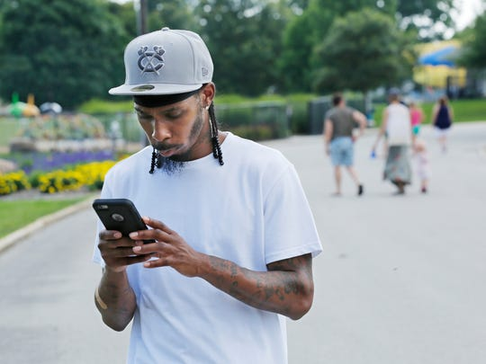 "Nell Clancy plays the new Pokémon Go video game on his smart phone Monday, July 11, 2016, while wandering Columbian Park. Clancy said he has played the game for two days now. ""Three or four people stopped to ask me what I caught,"" said Clancy, 29."