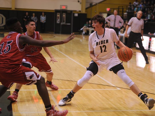 Rider's Ty Caswell steps back while guarded by Wichita Falls High's Taeshaun Johnson and Miguel Maldonado Friday, Jan. 20, 2017, at Rider. Rider defeated Old High 65-43.