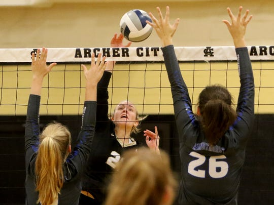 Archer City's Grace Morris spikes the ball past Windthorst's Kora Pennartz and Mollee Kirk Saturday, Sept. 30, 2017, in Archer City. The Trojanettes won in three sets, 25-22, 25-15, 25-14.