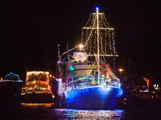 Boats festooned with holiday decorations plow through the water in Channel Islands Harbor during the annual Parade of Lights in 2017.