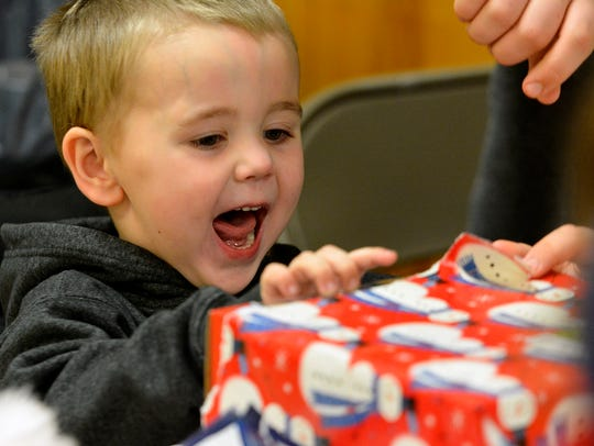 Bentley Fisher, 3, opens his gift from Santa during