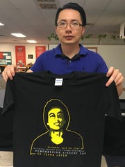 Kaikai Chen holds a t-shirt bearing the image of Vincent Chin.