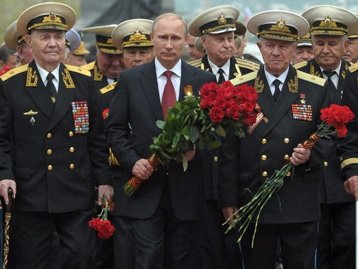 Russia's President Vladimir Putin and World War II veterans lay flowers at a war memorial during his visit to the Crimean port of Sevastopol on May 9.Crimea's largely Russian-speaking residents voted in March to become part of Russia in a hastily organized referendum.