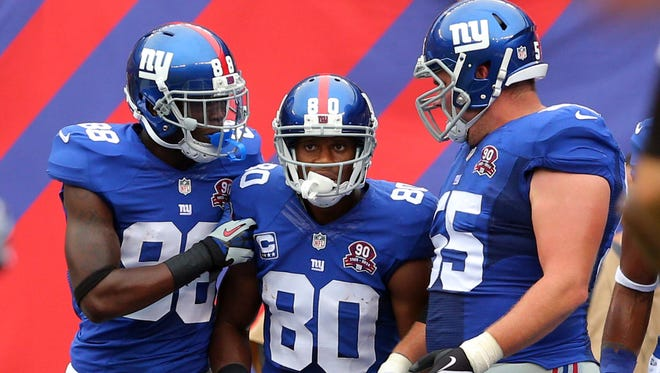 New York Giants wide receiver Victor Cruz (80) celebrates his touchdown against the Houston Texans with New York Giants wide receiver Corey Washington (88) and New York Giants center J.D. Walton (55) during the second quarter at MetLife Stadium.