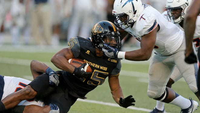 Southern Miss running back Ito Smith (25) is tackled by UTEP Miners linebacker Alvin Jones (16) and defensive back Jerrell Brown (18) the first half at M. M. Roberts Stadium.