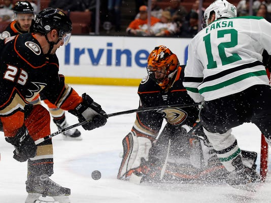 Dallas Stars center Radek Faksa, right, of the Czech Republic, has his shot blocked by Anaheim Ducks goaltender Ryan Miller, second from right, with defenseman Francois Beauchemin helping the goalie during the first period of an NHL hockey game in Anaheim, Calif., Wednesday, Feb. 21, 2018. (AP Photo/Alex Gallardo)