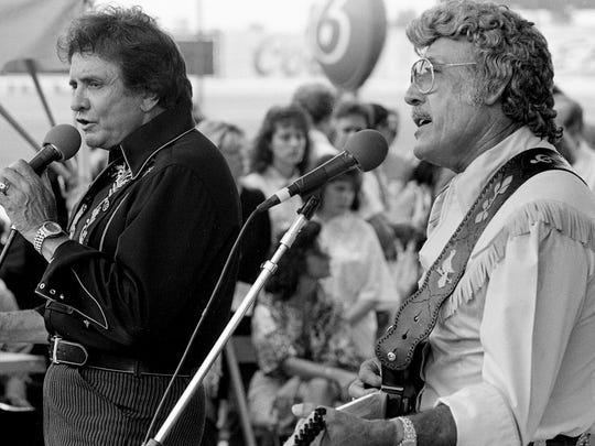 "Johnny Cash, left, sings with fleet-fingered Carl Perkins on ""I'll Fly Away at Fan Fair June 10, 1986. The superstars were surprise guests with fellow ""Memphis Homecoming"" artist Jerry Lee Lewis at the Mercury/PolyGram Records show at the Fairgrounds."