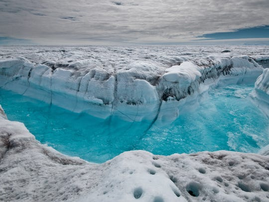 Surface melt water rushes along the Greenland ice sheet