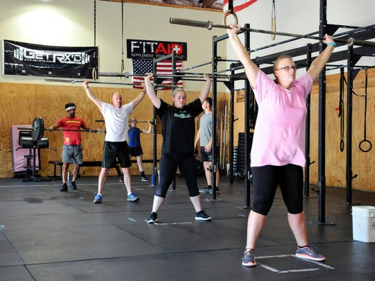 In this July 10, 2017, photograph, a class at CrossFit