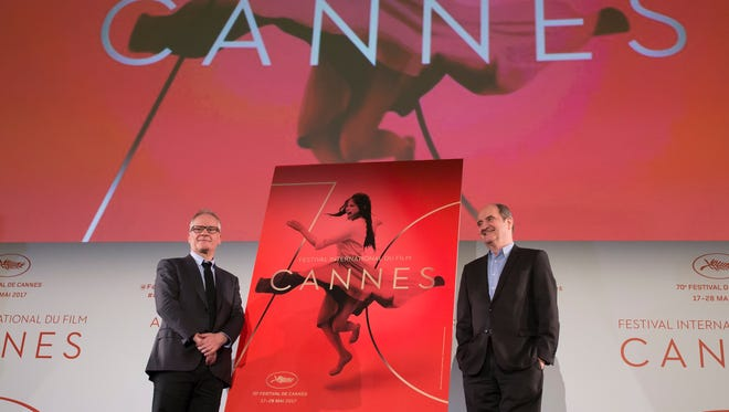 General Delegate of the Cannes Film Festival Thierry Fremaux and Cannes Festival President Pierre Lescure pose with the festival poster after announcing the film selection running in competition at the upcoming 70th Cannes Film Festival.