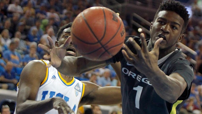 Oregon forward Jordan Bell, right, battles UCLA guard Isaac Hamilton for the ball during the first half of an NCAA college basketball game in Los Angeles, Saturday, Feb. 14, 2015.