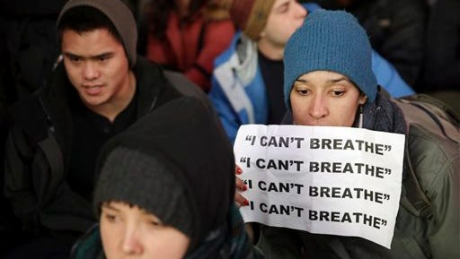 """FILE - In this Dec. 3, 2014 file photo, a person carries a sign inscribed with, """"I can't breathe,"""" during in a protest in response to the grand jury's decision in the Eric Garner case, in Times Square in New York. The exclamation made by Garner, while being placed in a police chokehold, was chosen as the most notable quote of the year in an annual list released Tuesday, Dec. 9, 2014, by a Yale University librarian. (AP Photo/Seth Wenig, File)"""