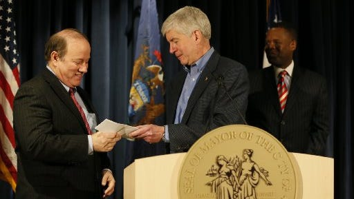 Gov. Rick Snyder hands Detroit Mayor Mike Duggan a check for $1.2 million, the savings Snyder said the city incurred by leasing the Mound Road detention center