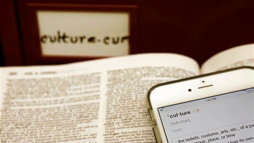 """This photo shows Merriam-Webster's 2014 word of the year, """"culture,"""" on the Merriam-Webster smartphone app and a  dictionary's culture page in front of the word's citation file drawer at the dictionary publisher's offices in Springfield, Mass. Citation files are notations of marked words used in context over time. Merriam-Webster based its pick and nine runners-up on significant increases in lookups this year over last at its homepage, Merriam-Webster.com."""