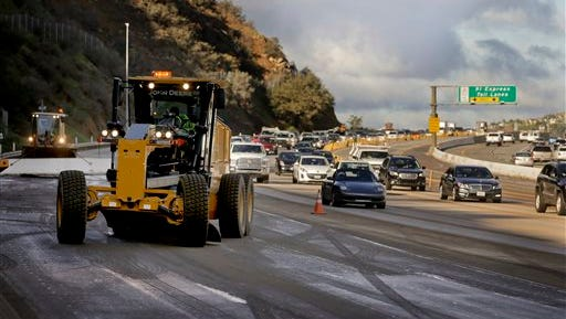 Caltrans crews work to clean up a torrent of mud and rocks covering part of State Route 91 in Orange County early today in Yorba Linda, Calif. Cars and trucks were stuck for several hours, but no injuries were reported.