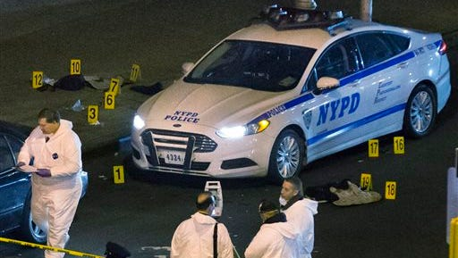 Bulletproof vests lie on each side of an NYPD patrol car as investigators work at the scene where two NYPD officers were shot in the Bedford-Stuyvesant neighborhood of the Brooklyn borough of New York on Saturday.