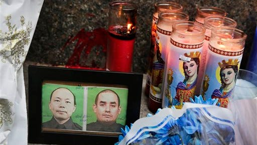 Photographs of slain New York Police officers Wenjian Liu, left, and Rafael Ramos are placed in a makeshift memorial honoring the men at the 84th Precinct in the Brooklyn borough of New York, where the officers were stationed,