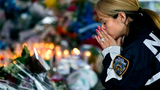 New York Police Department Lt. Tanisha Gurley visits a makeshift memorial near the site where NYPD officers Rafael Ramos and Wenjian Liu were murdered in the Brooklyn borough of New York.