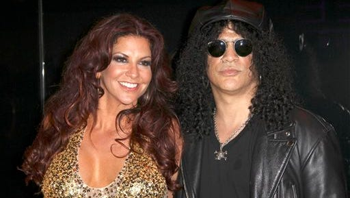 In this file photo, musician Slash right, and Perla Hudson arrives at the launch of Marquee, The Star entertainment venue in Sydney, Australia. Guitarist Slash has filed for divorce from his wife of 13 years. Court documents filed Tuesday in Los Angeles cite irreconcilable differences for Slash and Hudson's split.